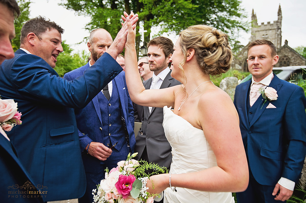 Documentary wedding photo of bestman congratulating bride with high five