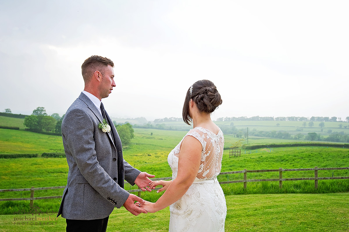 beautiful bride and groom holding hands looking over Dorset valley
