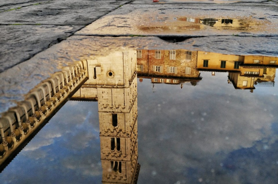 Mobile phone photo of church tower in Lucca reflected in a puddle.