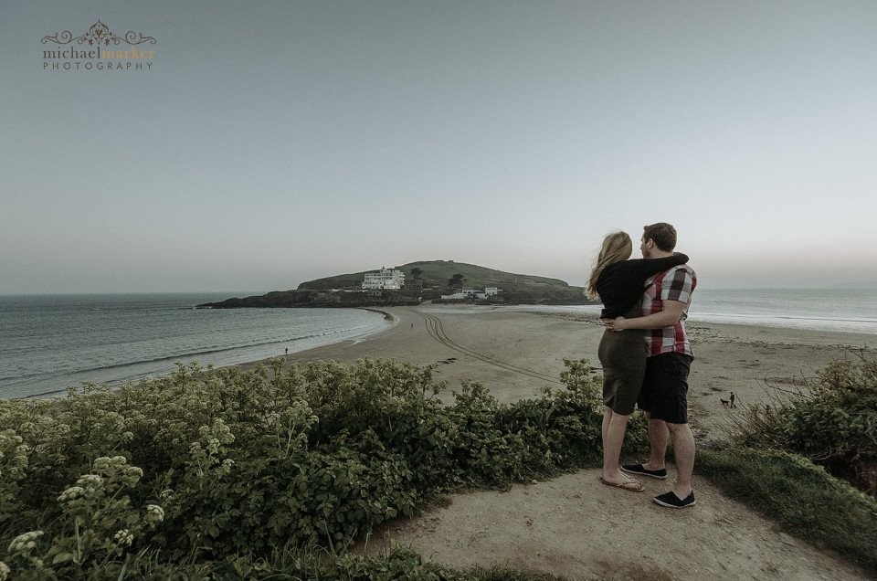 Engaged couple embracing looking towards Burgh Island from Bigbury beach top