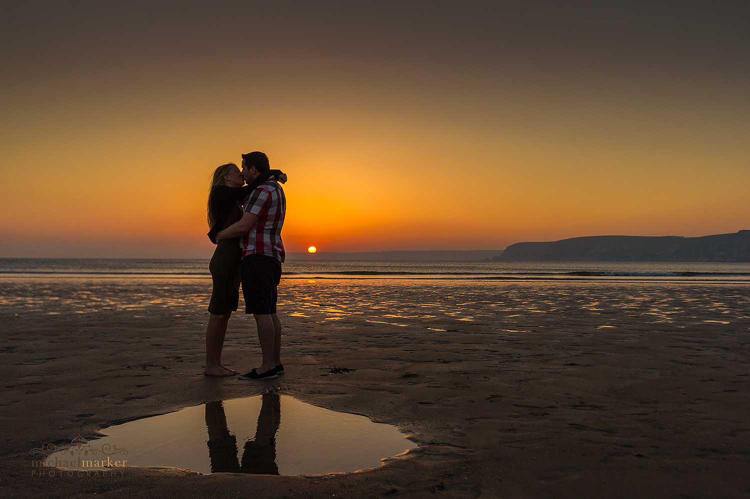 Engaged couple kiss at sunset with Burgh Island in Devon behind