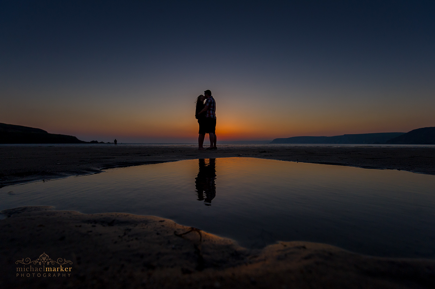 Enaged couple kiss at sunset on devon beach