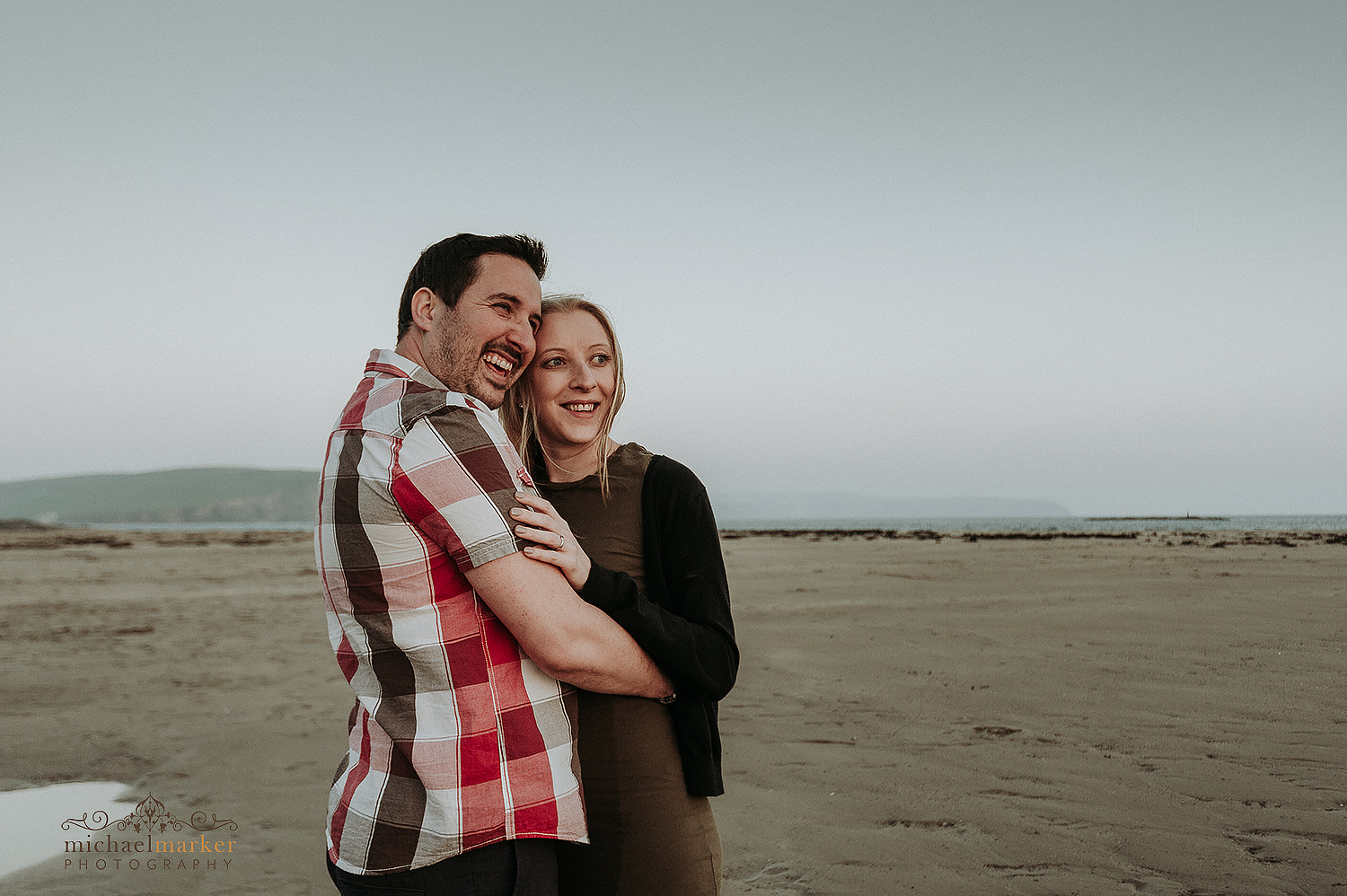 engaged couple on beach embrace and laughing