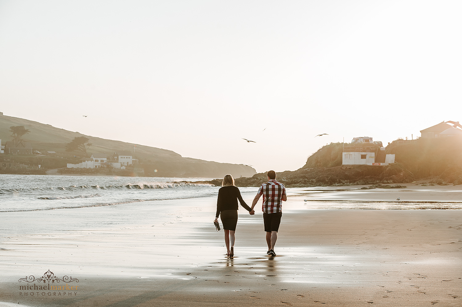 A couple walking towards the sunset on Bigbury beach