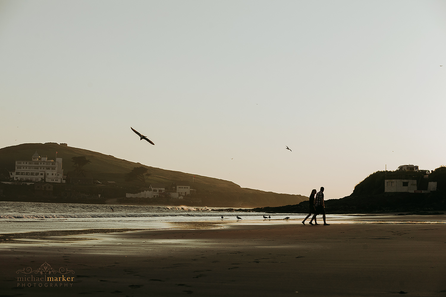 Man and lady walking in Bigbury beach in Devon at Sunset