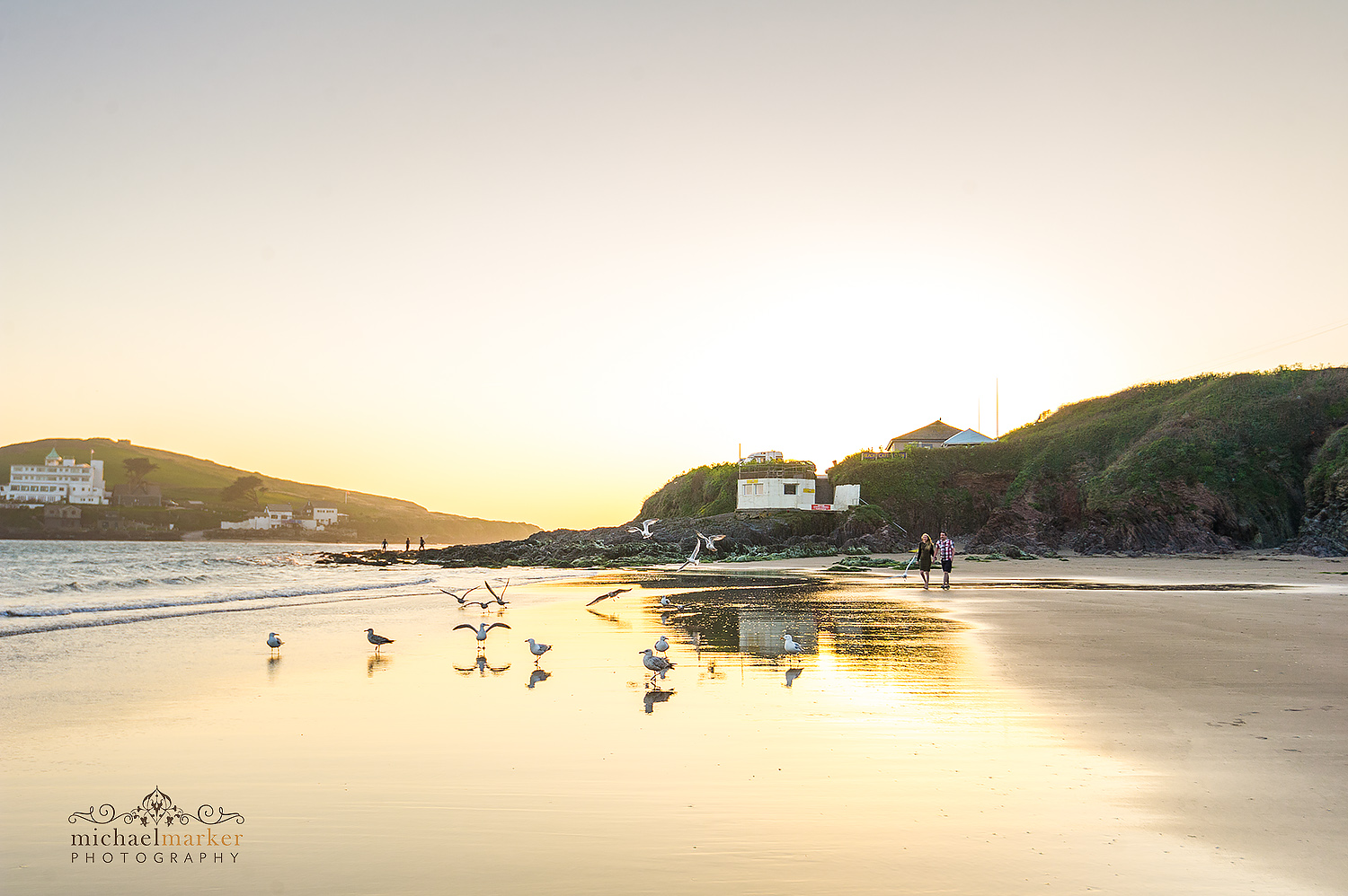 Couple walking along Bigbury beach at sunset