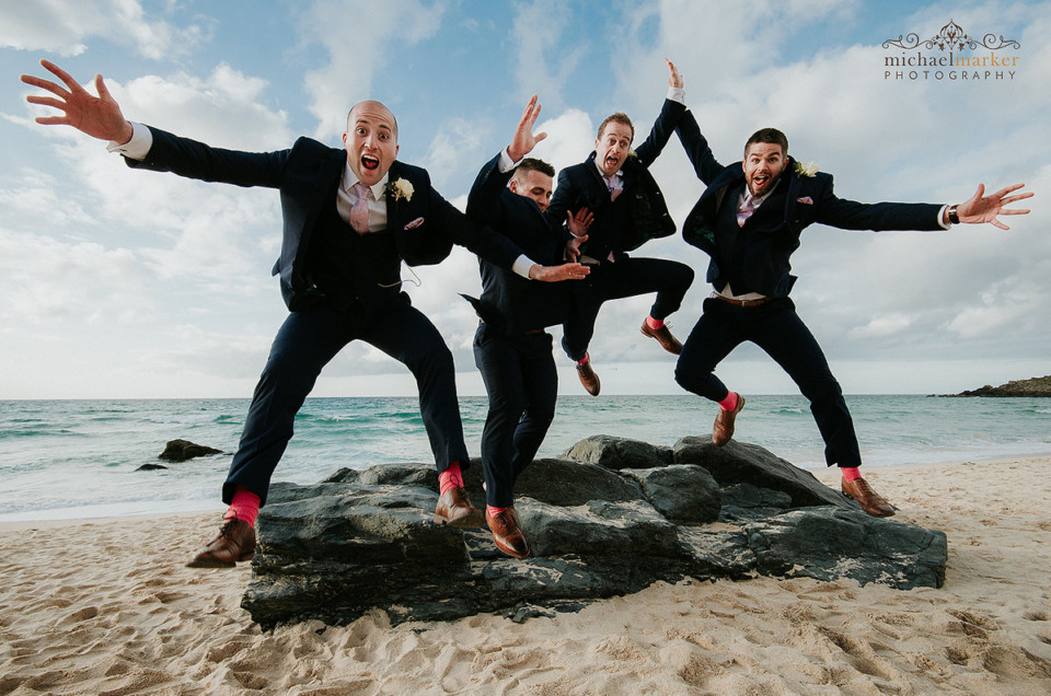 Groomsmen jumping towards the camera lens at St Ives Easter wedding