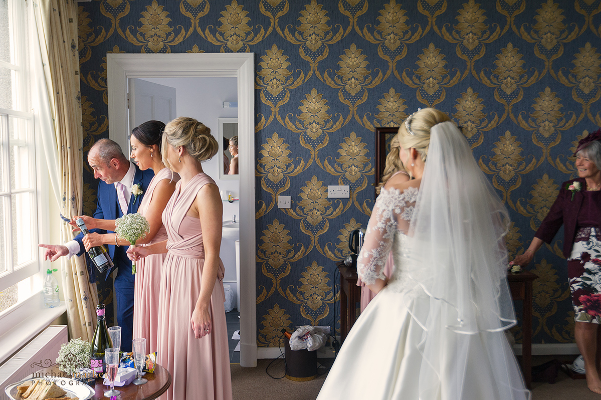 Father and bridesmaids opening bottle of prosecco and looking out window. Bride and mother look on.