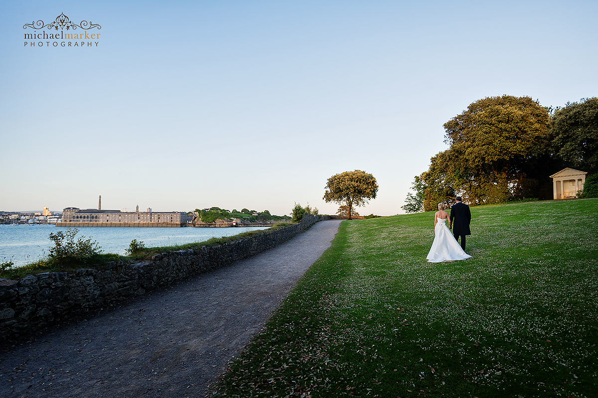 Wedding couple walk beside the Tamar River with the Royal William Yard in the background.