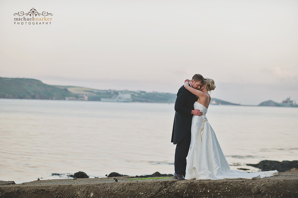 Plymouth weddign couple embrace by the waterfront with the Plymouth Sound in the background.