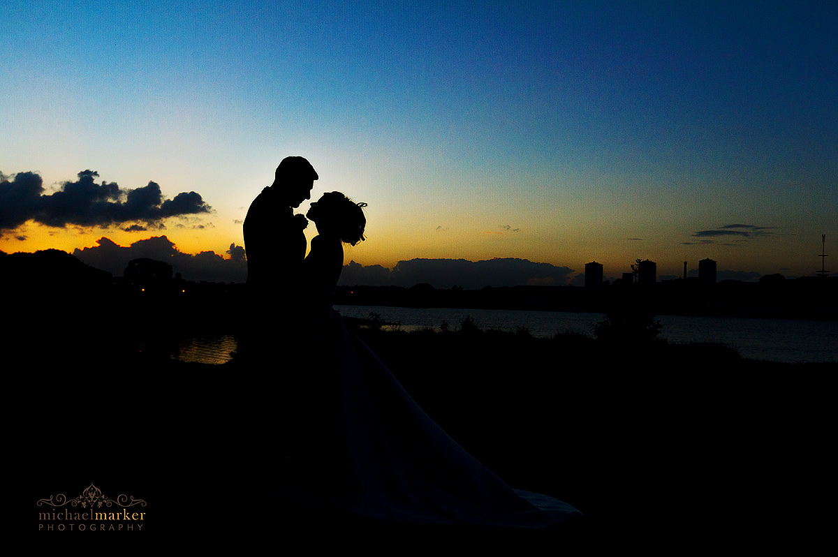 Bride and groom silhouette at sunset on the River Tamar. Colourful sky.