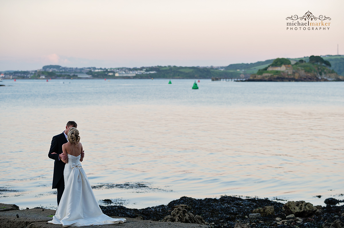 Bride and groom kiss at dusk on the Plymouth waterfront on their wedding day.