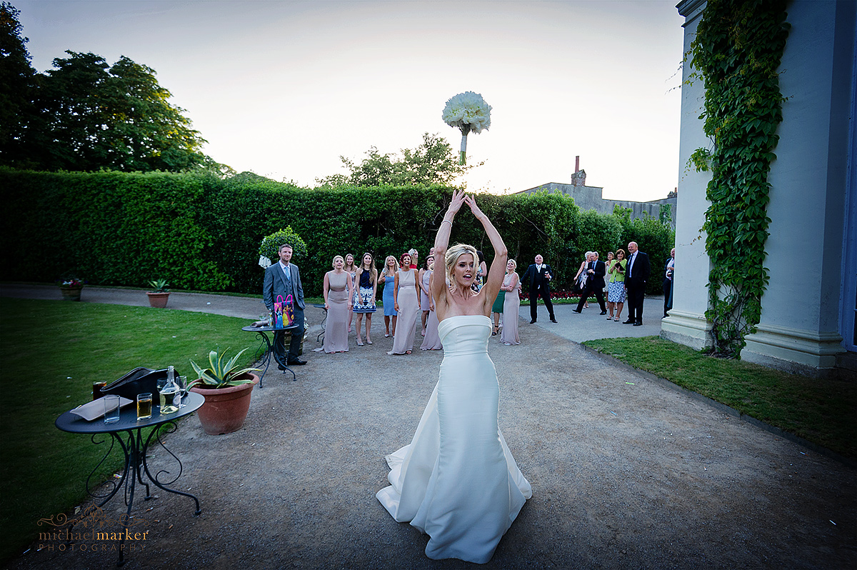 Bride throwing the wedding bouquet as women guests wait to catch it outside Mount Edgcumbe Orangery