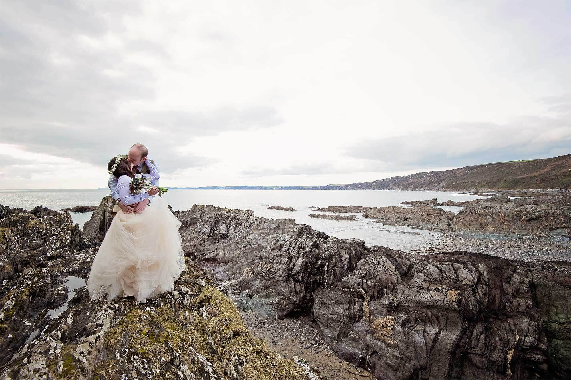 Bride and groom kiss on rocks at Cornish beach wedding at Polhawn Fort.