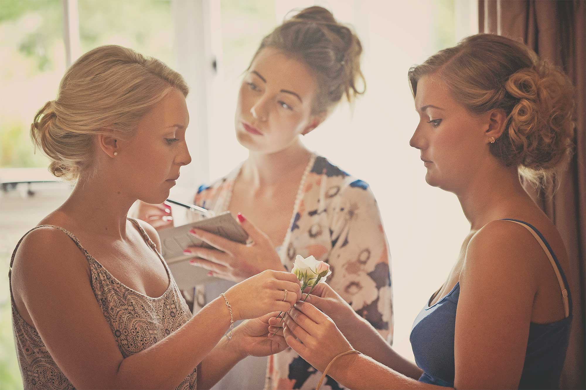Bride and bridesmaids apply make up whilst getting ready for Tavistock wedding in Devon.