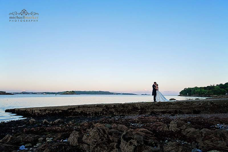 Bride and groom embrace at Plymouth waterfront at dusk.