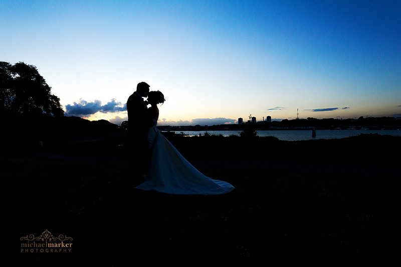 Bride and groom tender kiss at Mount Edgcumbe wedding at sunset overlooking Plymouth skyline.