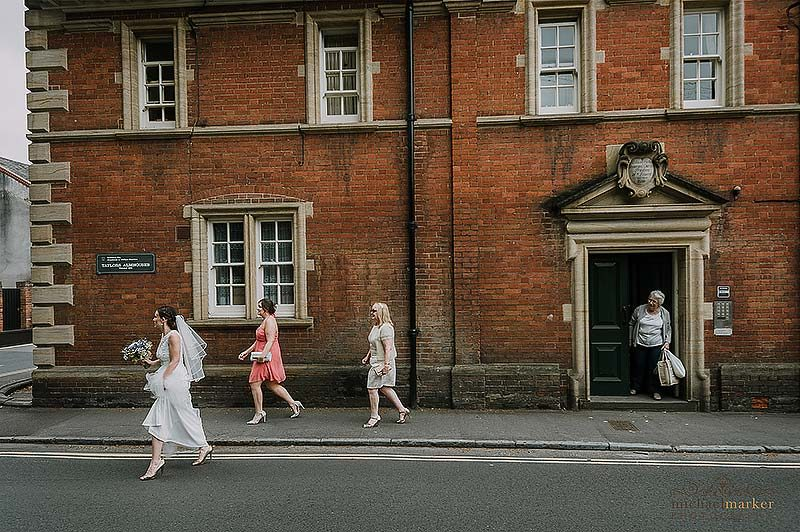 Bride, bridesmaid and mother walk through Salisbury to the wedding ceremony whilst a passerby looks on.