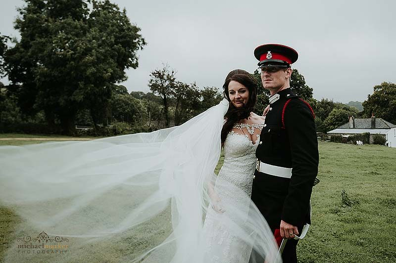 Brides veil blows in breeze during Cornish military wedding