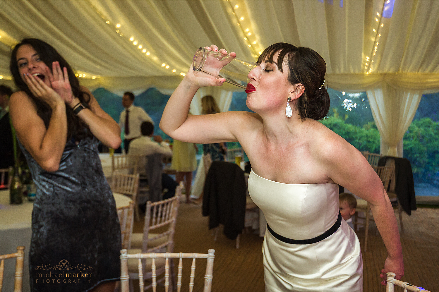 Bride downing a pint of beer at Pentillie wedding marquee