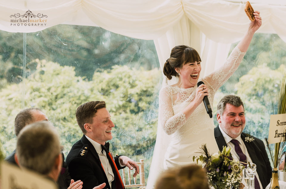 Bride holds piece of toast during her wedding speech at Pentillie Castle wedding