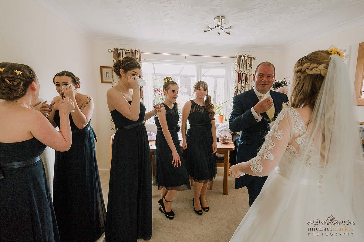bridesmaids and father of bride crying when seeing bride for first time
