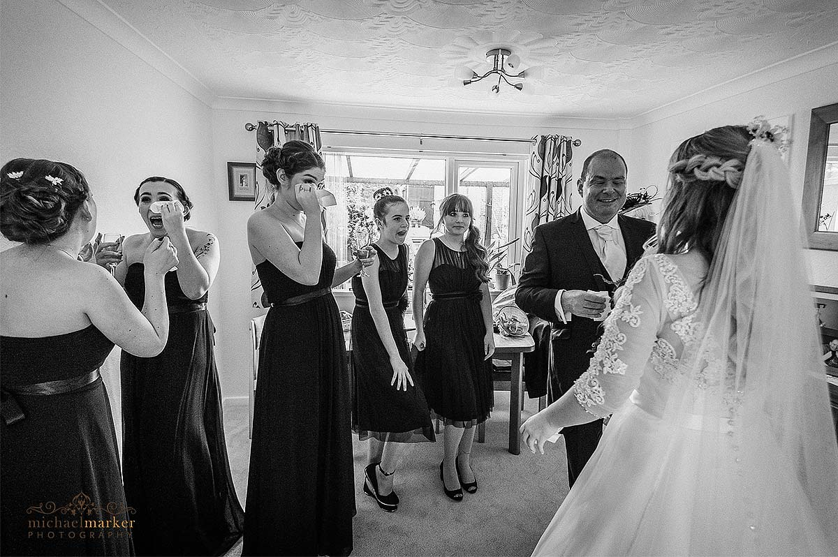 Bridesmaid and father wiping tears when seeing the bride for first look