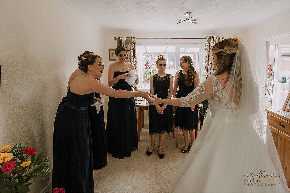 bride and bridesmaids passing tissues to wipe tears.