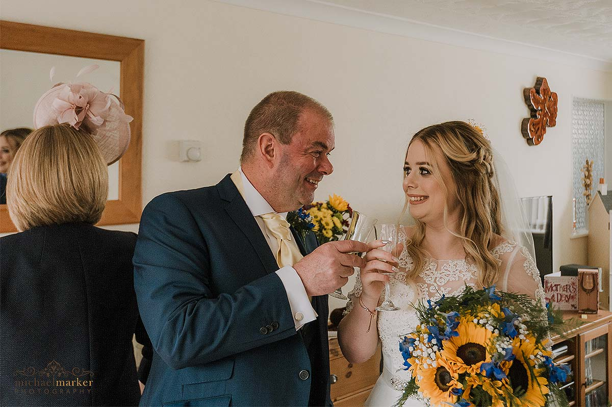 emotional father and bride looking at each other and toasting bucks fizz