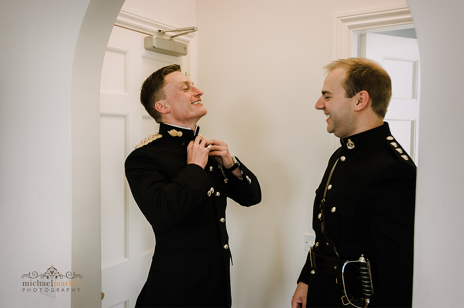Military officer wedding groom getting dressed with help of his bestman at Pentillie Castle in Cornwall.