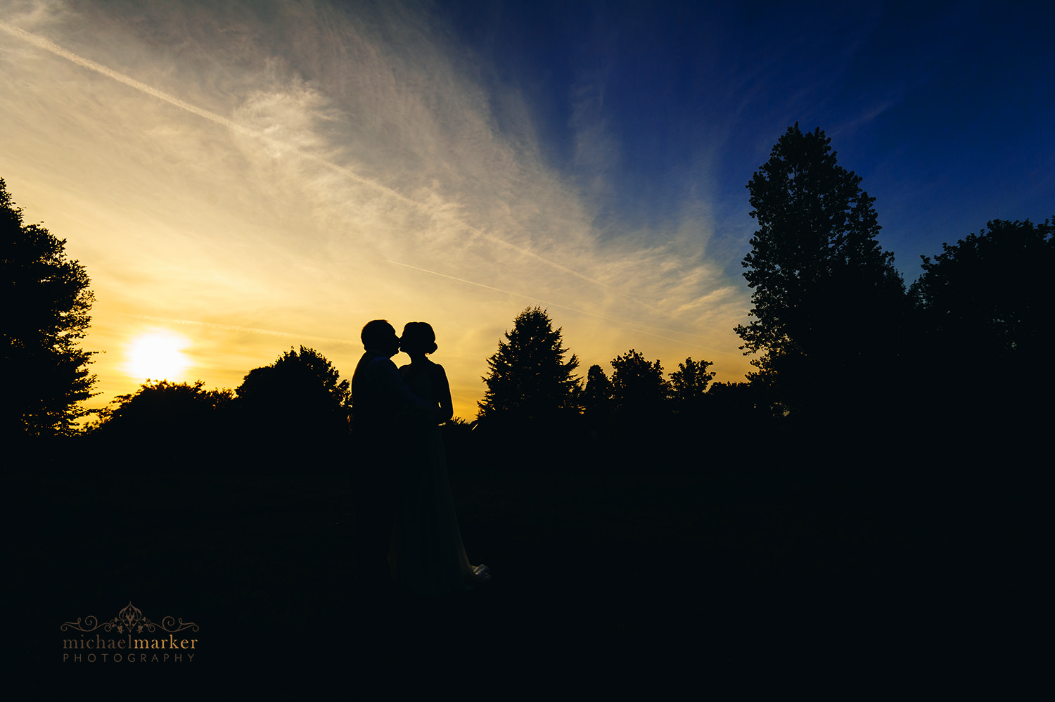 Silhouette of bide and groom kissing at Sunset at Buckinghamshire wedding.