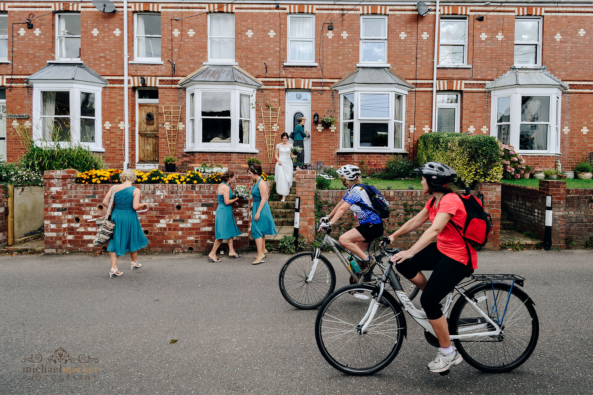 Exeter wedding photographers documentary photo of cyclists riding past bride and bridesmaid as they leave home .