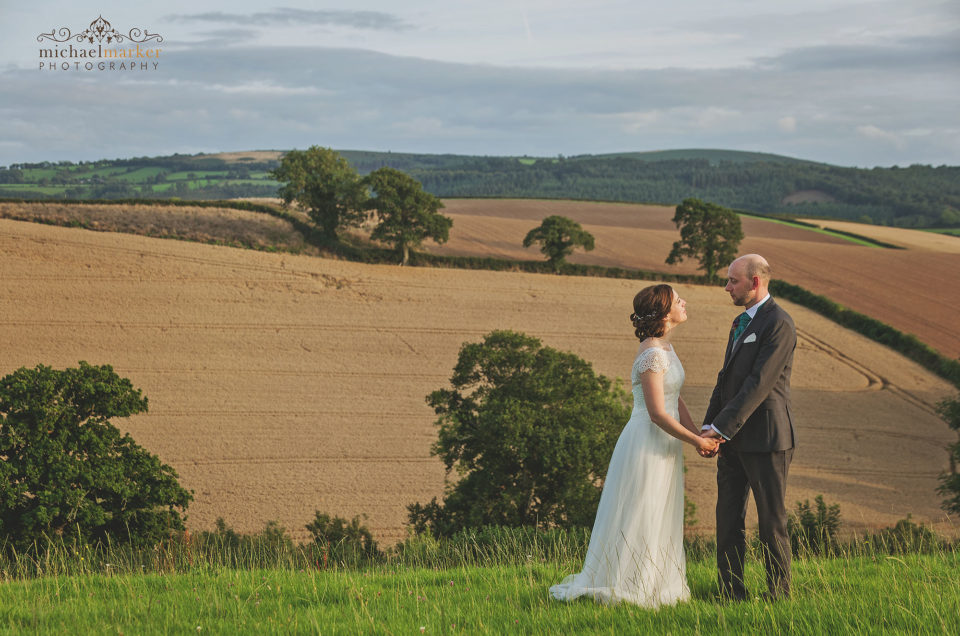 Bride and groom hold hands and look at each other in field at Higher Egbbeer in devon.