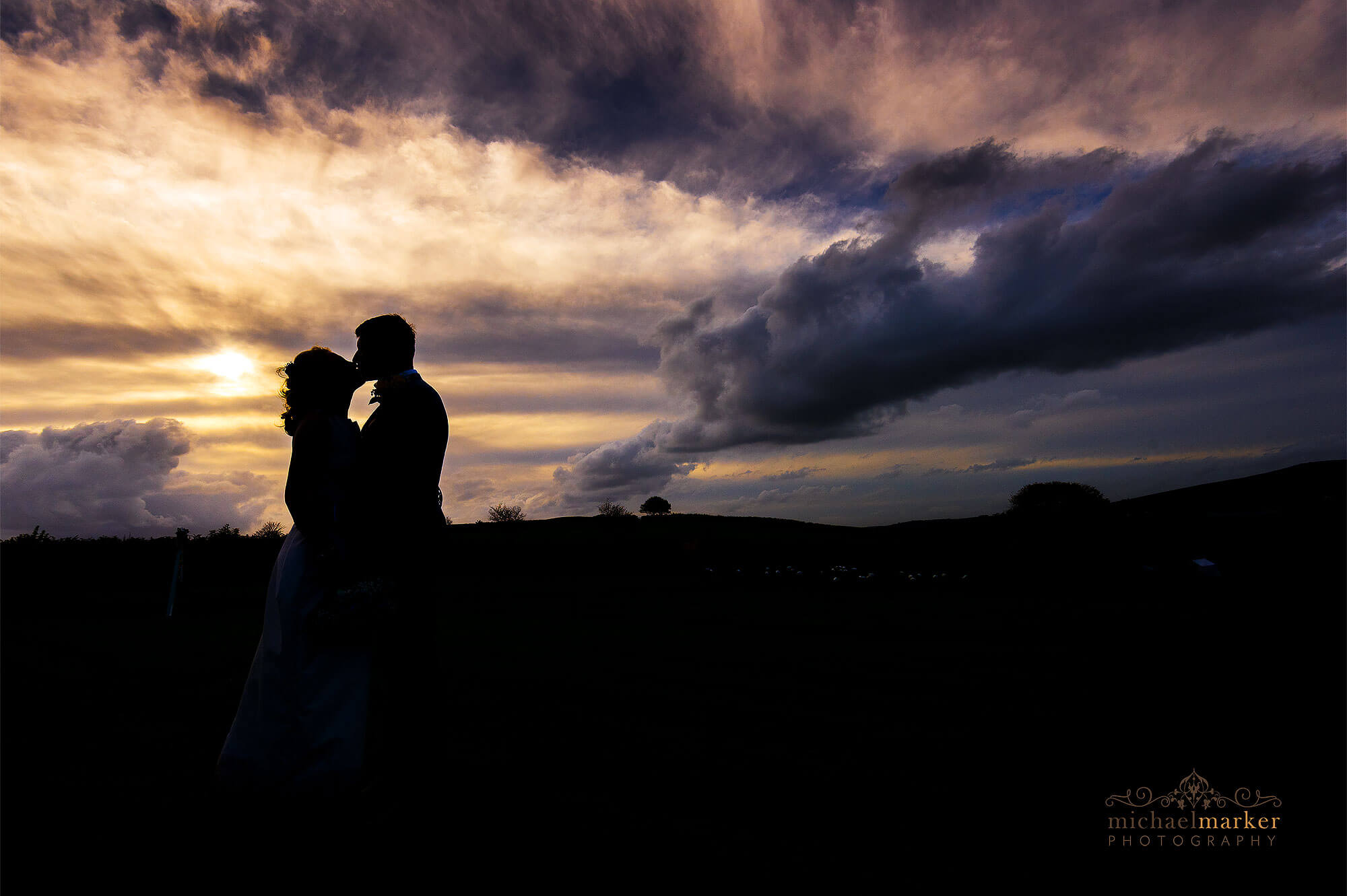 Devon wedding photographers sunset silhouette of bride and groom kissing at Dunwell Farm wedding venue