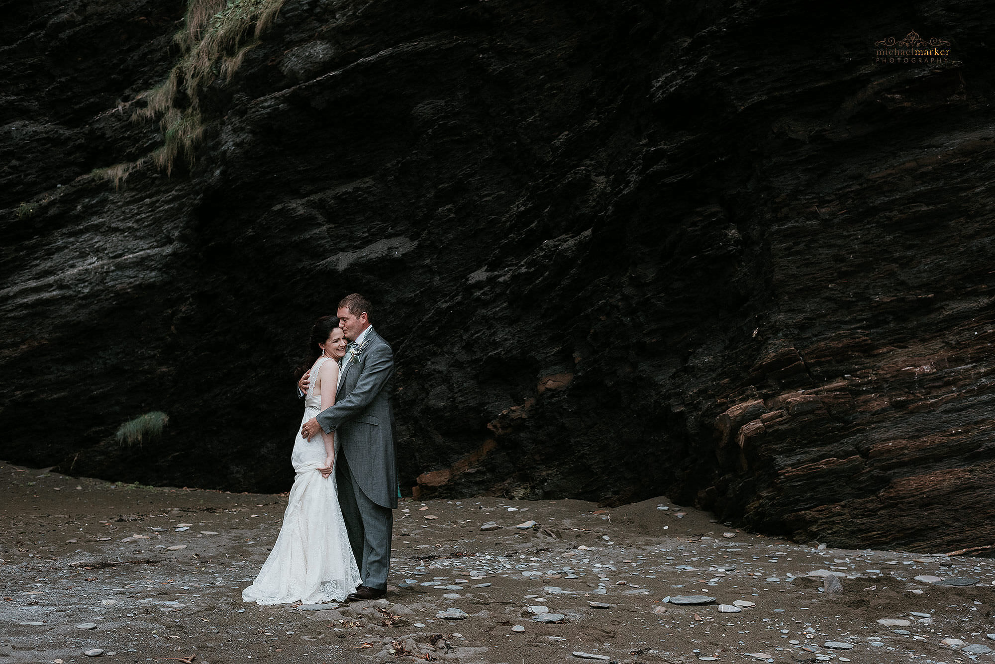 Bride and groom kiss on secluded North Devon beach at their Autumn beach wedding.