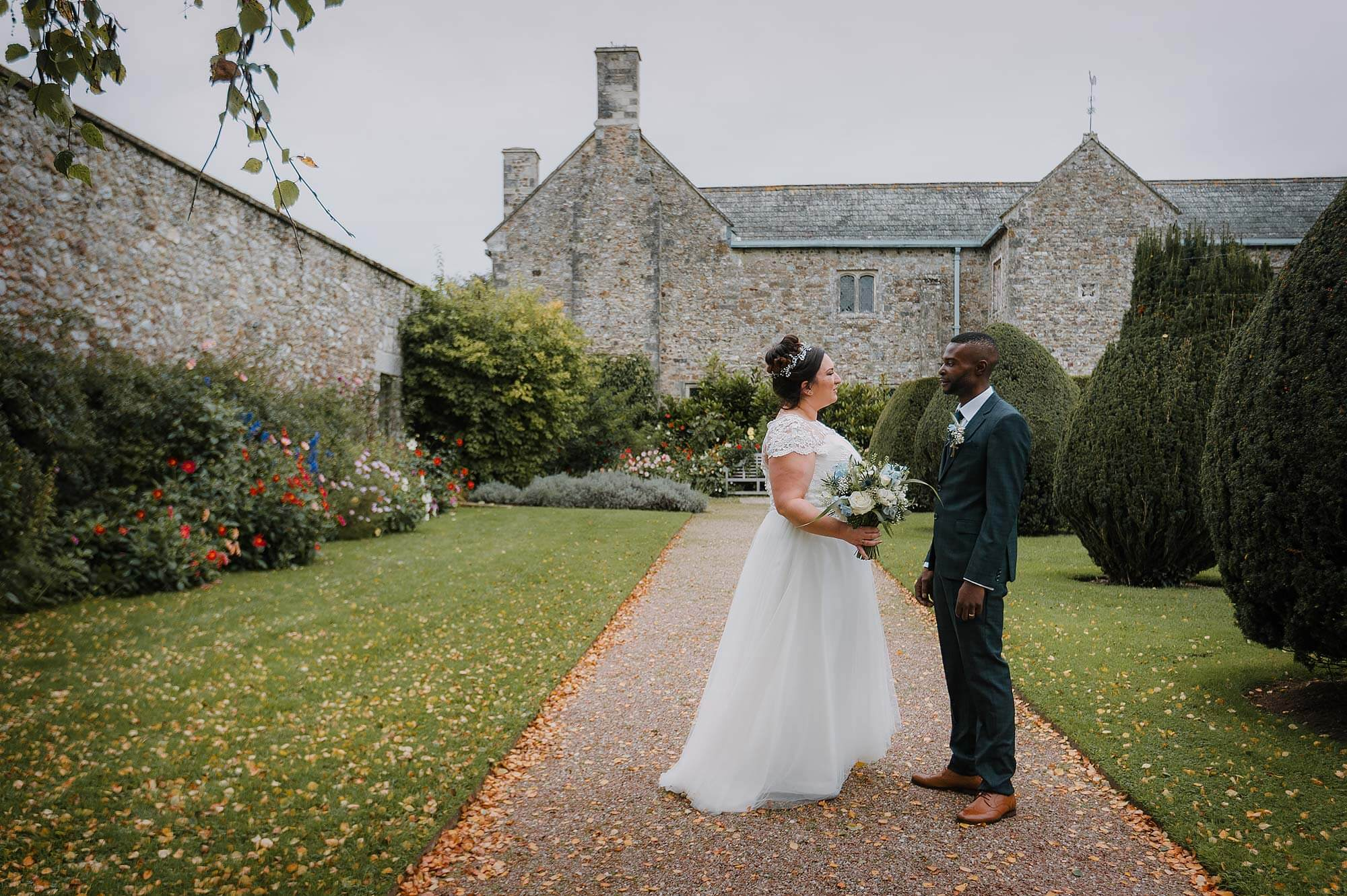 Bride and groom in front of Cadhay House in Devon