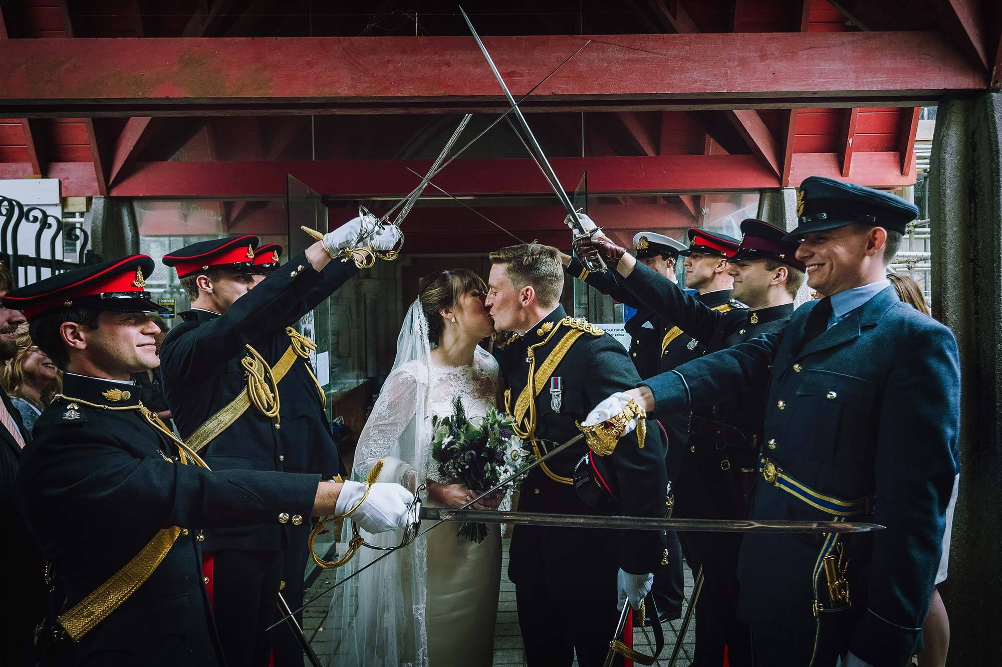 Groom and bride kiss outside Catholic Cathedral in Plymouth as part of Army tradition.