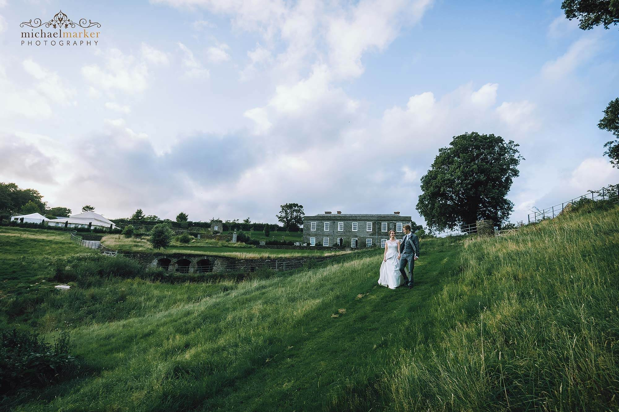 Bride and groom walking in the fields of luxury wedding venue Shilstone House.
