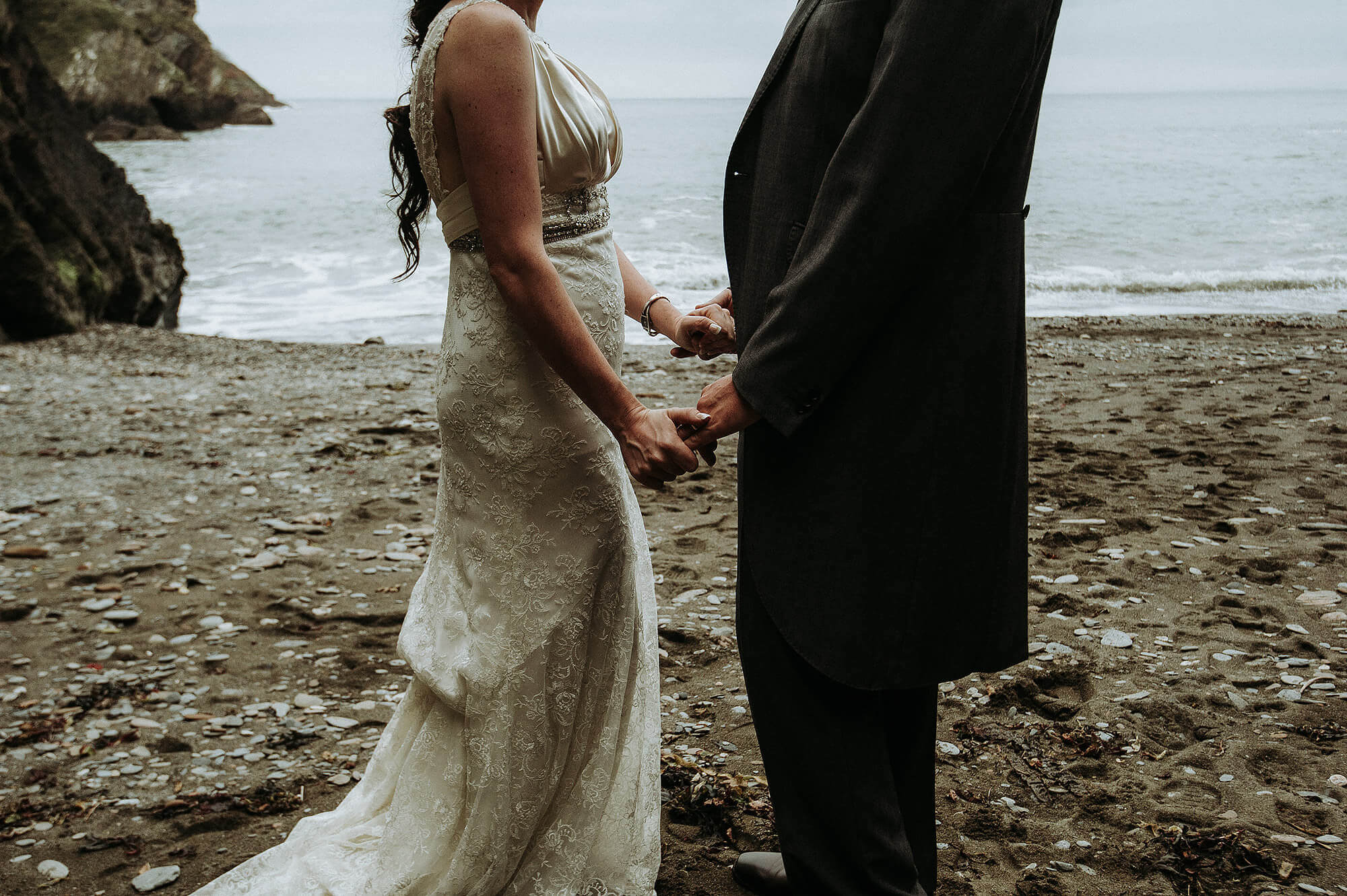 Couple holding hands on secluded North Devon beach on their wedding day