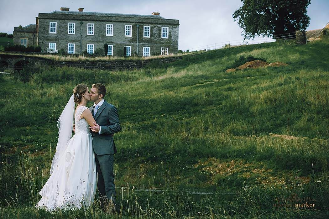 tender-wedding-kiss-in-fields-at-Shilstone-House