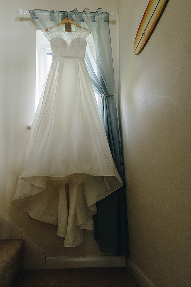 Devon brides wedding dress hanging on the staircase