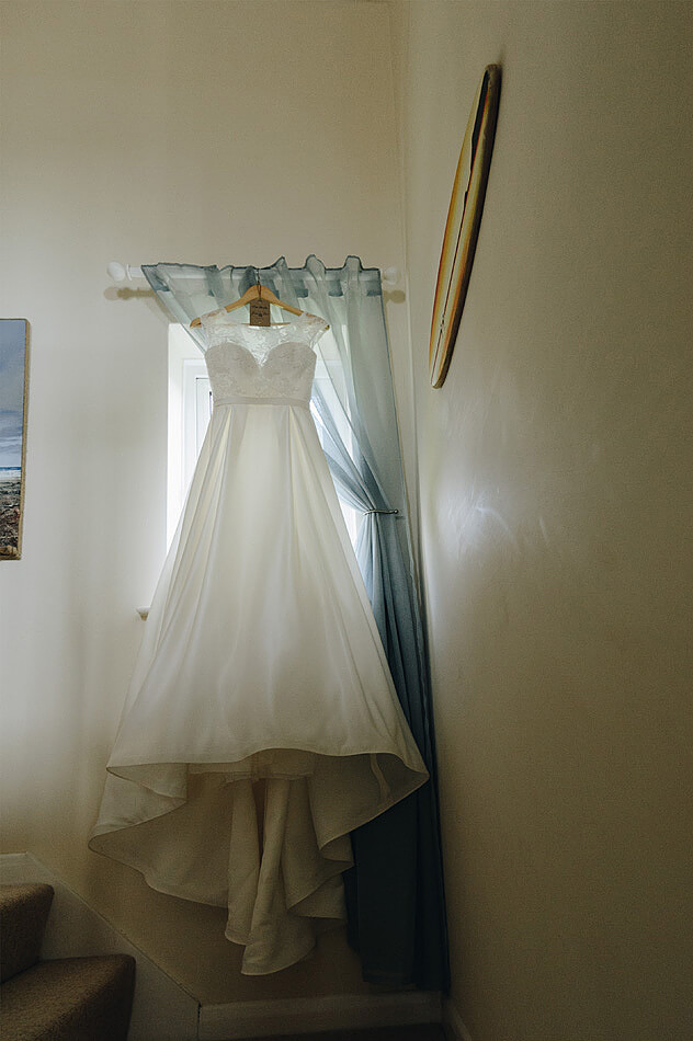 Brides wedding dress hanging up on the stairs in devon