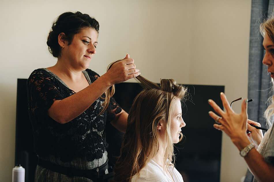 wedding hairstylist doing brides hair in Devon