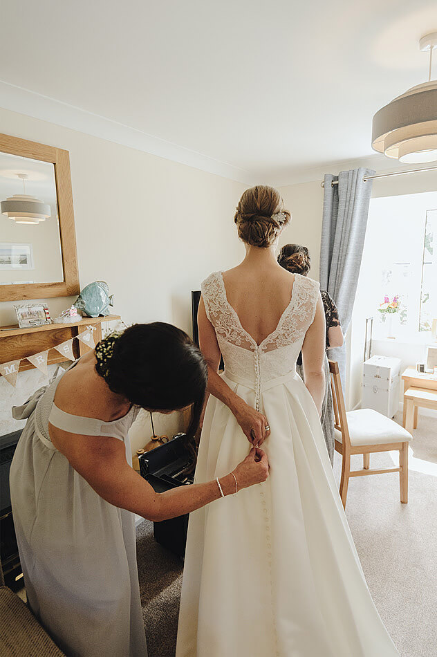 Bridesmaid buttoning the back of the wedding dress before the Devon wedding at Shilstone