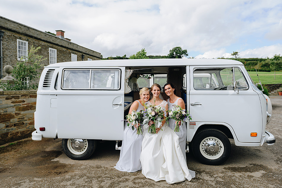 bride and bridesmaids in front of Shilstone House with campervan