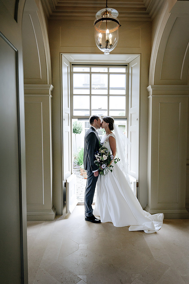 bride and groom kiss in hall of Shilstone House