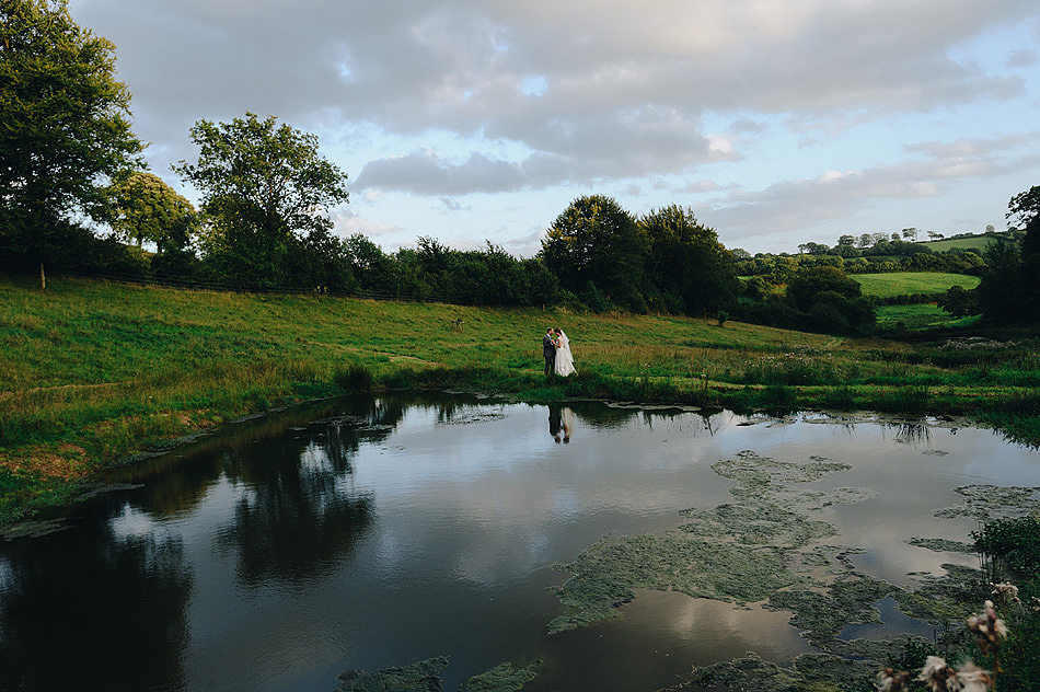 bride and groom reflected in the ponds at Shilstone House wedding venue