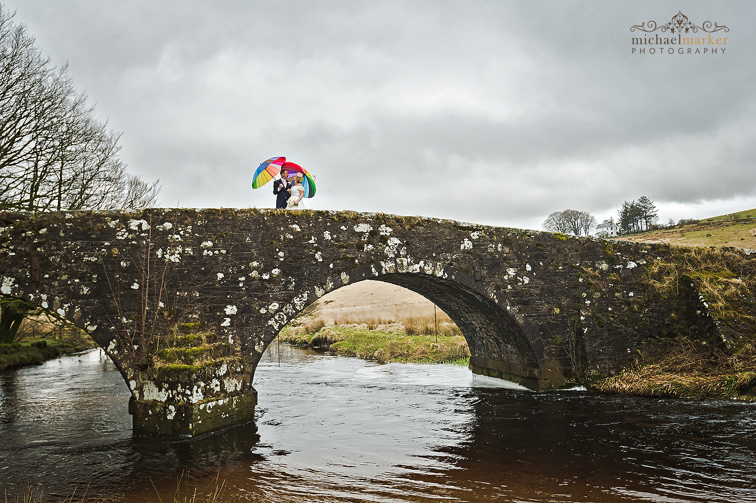 Bride and groom and colourful umbrellas on bridge at Two Bridges Hotel on Dartmoor.