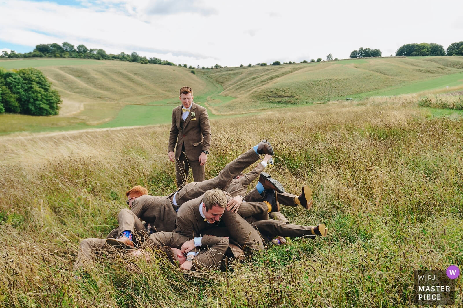 Groomsmen pile on top of each other at Wiltshire wedding. award winning photograph from WPJA