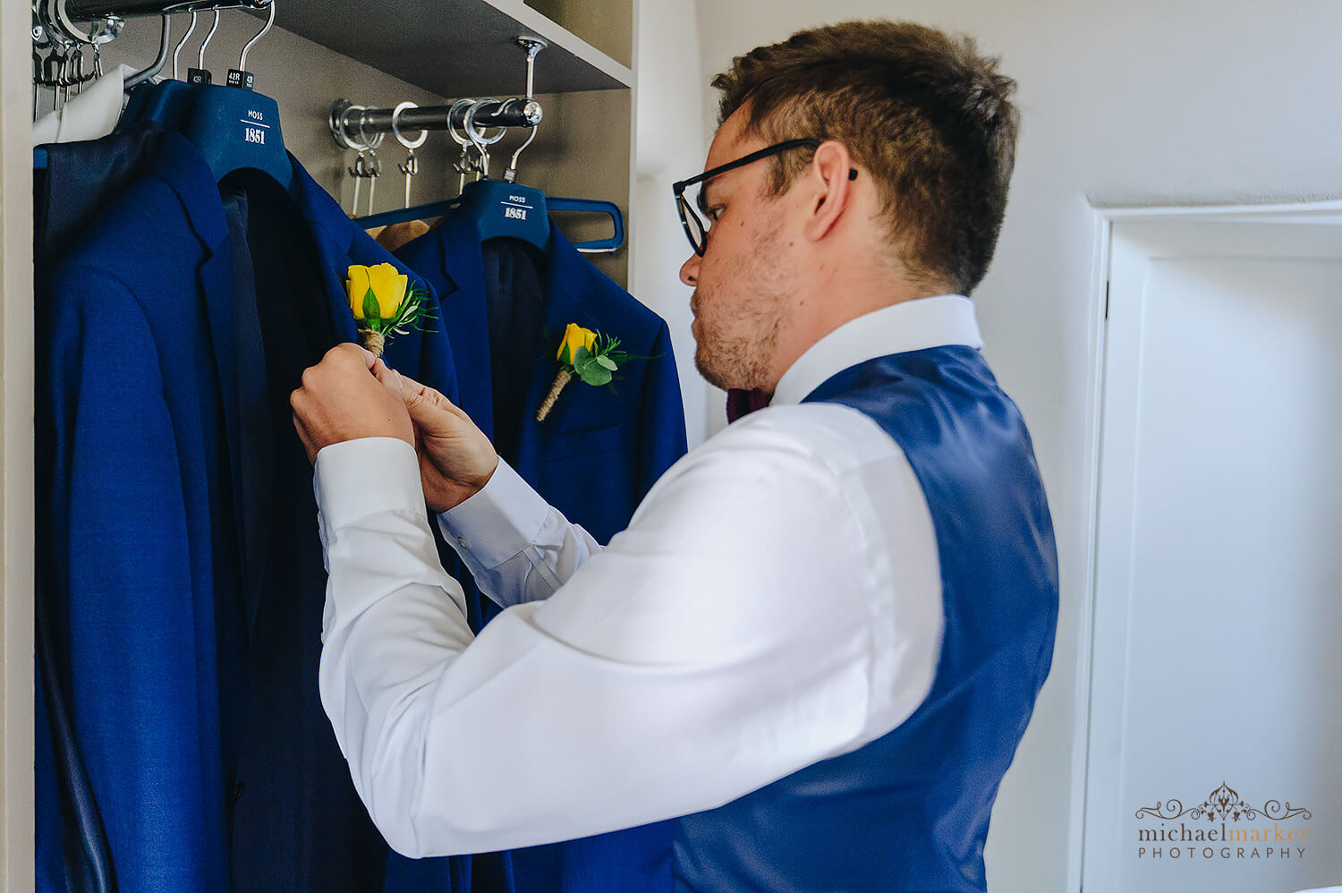 Groom attaching hand tied yellow rose button hole to his jacket at Trevenna
